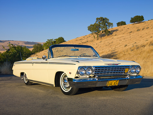 AUT 22 RK2891 01 © Kimball Stock 1962 Chevrolet Impala Convertible Yellow 3/4 Front View On Pavement By Hills