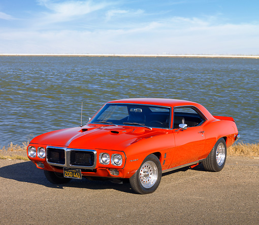 AUT 22 RK2898 01 © Kimball Stock 1969 Pontiac Firebird Red 3/4 Front View On Pavement By Water