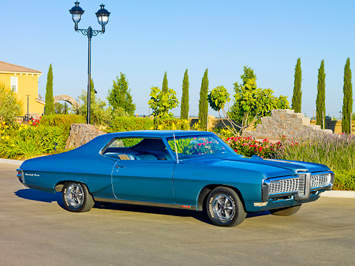 AUT 22 RK2922 01 © Kimball Stock 1968 Pontiac Grand Prix Blue 3/4 Front View On Pavement By Garden