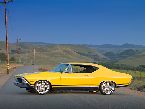 AUT 22 RK3044 01 © Kimball Stock 1968 Chevrolet Chevelle SS 396 Yellow Profile View On Road By Grassy Hills