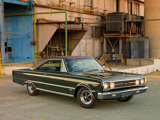AUT 22 RK3088 01 © Kimball Stock 1967 Plymouth Hemi GTX Dark Green 3/4 Front View On Pavement By Old Factory Building