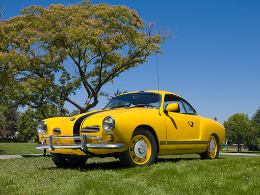 AUT 22 RK3112 01 © Kimball Stock 1967 VW Karmann Ghia Coupe Yellow With Black Stripe 3/4 Front View On Grass By Tree
