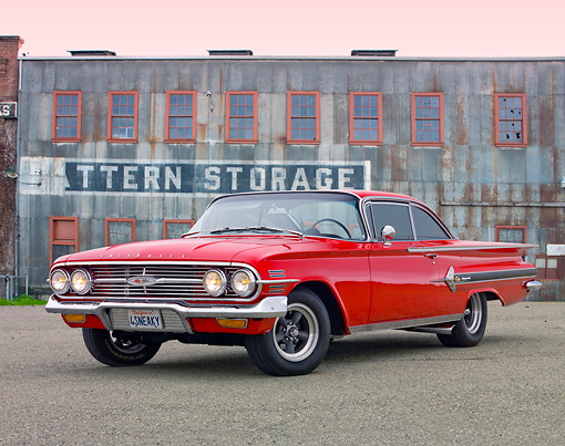 AUT 22 RK3149 01 © Kimball Stock 1960 Chevrolet Impala Red 3/4 Front View On Pavement By Old Building