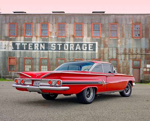 AUT 22 RK3152 01 © Kimball Stock 1960 Chevrolet Impala Red 3/4 Rear View On Pavement By Old Building