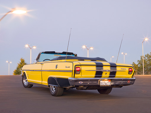 AUT 22 RK3158 01 © Kimball Stock 1963 Chevrolet Nova SS Convertible Yellow With Black Stripes 3/4 Rear View On Pavement At Dusk