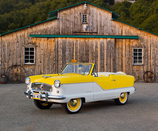 AUT 22 RK3168 01 © Kimball Stock 1960 Nash Metropolitan Yellow And White 3/4 Front View On Pavement By Old Barn