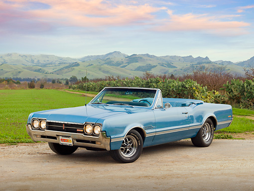 AUT 22 RK3171 01 © Kimball Stock 1966 Oldsmobile 442 Light Blue 3/4 Front View On Gravel By Grass Field And Hills