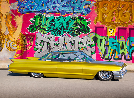 AUT 22 RK3184 01 © Kimball Stock 1961 Cadillac Coupe de Ville Gold Profile View On Pavement By Wall Of Graffiti