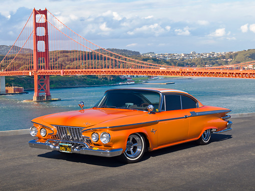AUT 22 RK3188 01 © Kimball Stock 1961 Plymouth Fury Orange Pearl 3/4 Front View On Pavement By Golden Gate Bridge