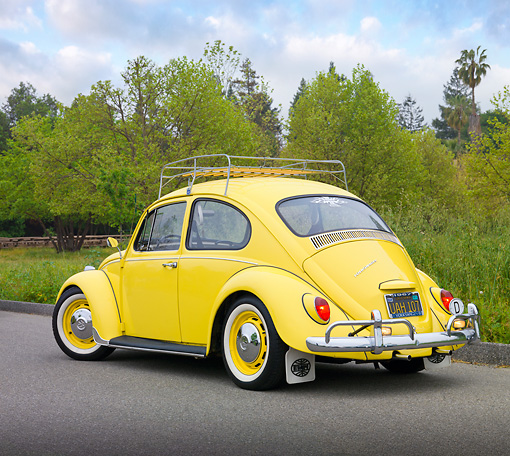 AUT 22 RK3227 01 © Kimball Stock 1967 VW Beetle Yellow 3/4 Rear View On Pavement By Trees