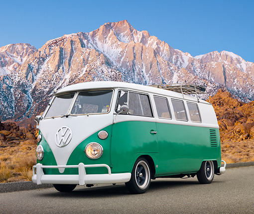 AUT 22 RK3238 01 © Kimball Stock 1965 VW Standard Bus Green And White 3/4 Front View On Pavement Snowy Mountain Peaks