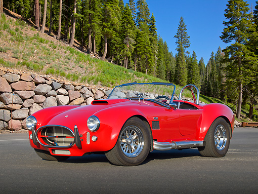 AUT 22 RK3286 01 © Kimball Stock 1965 AC Shelby Cobra MK3 Roadster Red (Monza) 3/4 Front View On Pavement By Pine Trees