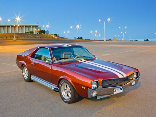 AUT 22 RK3305 01 © Kimball Stock 1969 AMC AMX Candy Tangerine With White Stripes 3/4 Front View In Parking Lot At Dusk