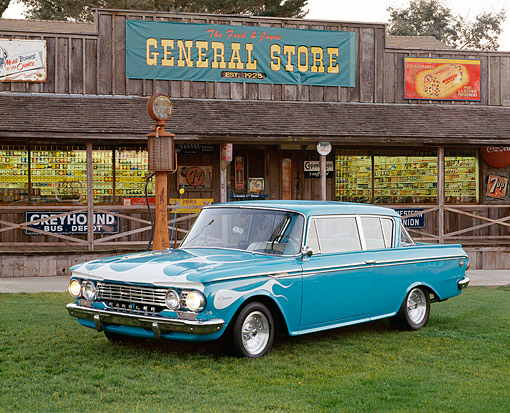 AUT 22 RK3367 01 © Kimball Stock 1962 AMC Rambler Classic Blue With White Flames 3/4 Front View On Grass By General Store