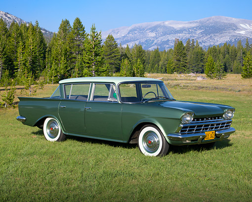 AUT 22 RK3382 01 © Kimball Stock 1960 AMC Rambler Deluxe Green 3/4 Front View On Grass By Evergreen Trees And Mountain