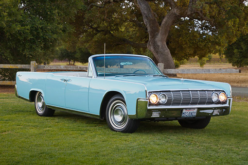 AUT 22 RK3415 01 © Kimball Stock 1964 Lincoln Continental Convertible Baby Blue 3/4 Front View On Grass By Trees