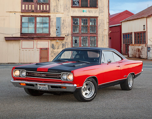 AUT 22 RK3445 01 © Kimball Stock 1969 Plymouth GTX Red With Black Stripes 3/4 Front View On Pavement By Old Factory Building