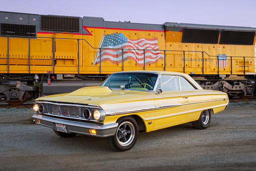 AUT 22 RK3448 01 © Kimball Stock 1964 Ford Galaxie 500 XL Factory Lightweight Banana Yellow Pearl 3/4 Front View On Pavement By Train