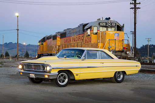 AUT 22 RK3449 01 © Kimball Stock 1964 Ford Galaxie 500 XL Factory Lightweight Banana Yellow Pearl 3/4 Side View On Pavement By Train