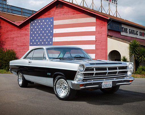 AUT 22 RK3468 01 © Kimball Stock 1967 Ford Fairlane 500 Silver And Black 3/4 Front View On Pavement By Building With American Flag