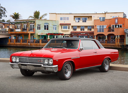 AUT 22 RK3469 01 © Kimball Stock 1965 Buick Skylark GS Red With Black Vinyl Roof 3/4 Front View On Pavement By Canal And Buildings