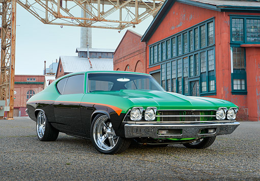 AUT 22 RK3477 01 © Kimball Stock 1969 Chevrolet Chevelle Green, Black And Orange 3/4 Front View On Pavement By Old Factory Building