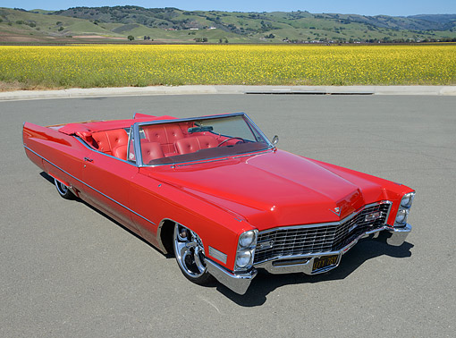 AUT 22 RK3501 01 © Kimball Stock 1967 Cadillac Coupe De Ville Red 3/4 Front View On Pavement By Field Of Wildflowers