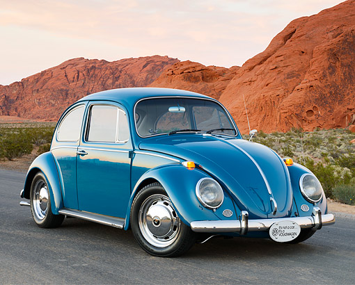 AUT 22 RK3548 01 © Kimball Stock 1966 Volkswagen Beetle Blue 3/4 Front View On Pavement By Red Rock At Dusk