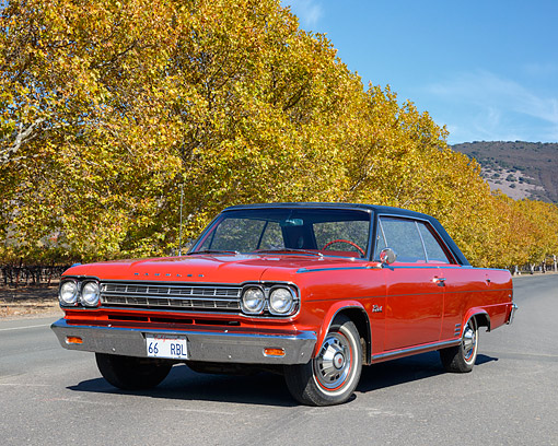 AUT 22 RK3591 01 © Kimball Stock 1966 AMC Rambler Rebel Hard Top Red On Pavement By Trees