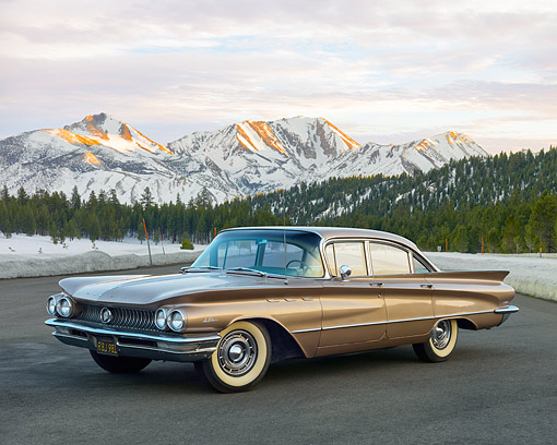 AUT 22 RK3644 01 © Kimball Stock 1960 Buick LeSabre Tahitian Beige 3/4 Front On Pavement By Snowy Mountains