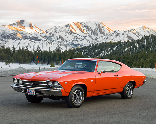 AUT 22 RK3656 01 © Kimball Stock 1969 Chevrolet Chevelle SS 396 Orange 3/4 Front View On Pavement By Snowy Mountains