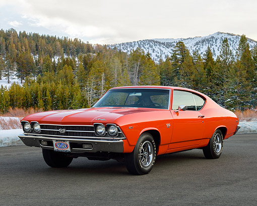 AUT 22 RK3657 01 © Kimball Stock 1969 Chevrolet Chevelle SS 396 Orange 3/4 Front View On Pavement By Snowy Mountains