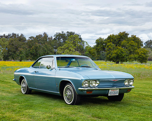 AUT 22 RK3668 01 © Kimball Stock 1965 Chevrolet Corvair Hard Top Light Blue 3/4 Front View On Grass