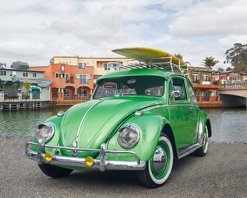 AUT 22 RK3744 01 © Kimball Stock 1965 Volkswagen Beetle Square Window Metallic Green 3/4 Front View By Water And Buildings