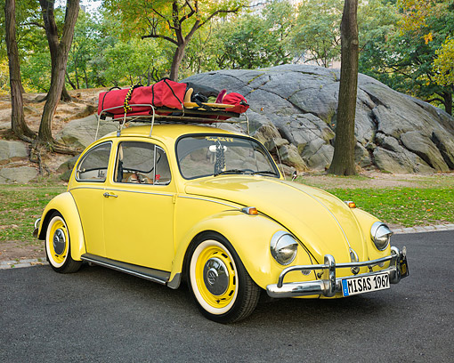 AUT 22 RK3754 01 © Kimball Stock 1967 Volkswagen Beetle With Rack Yellow 3/4 Front View On Road By Trees