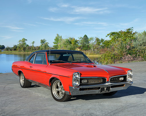 AUT 22 RK3790 01 © Kimball Stock 1967 Pontiac GTO Red 3/4 Front View On Pavement By Lake