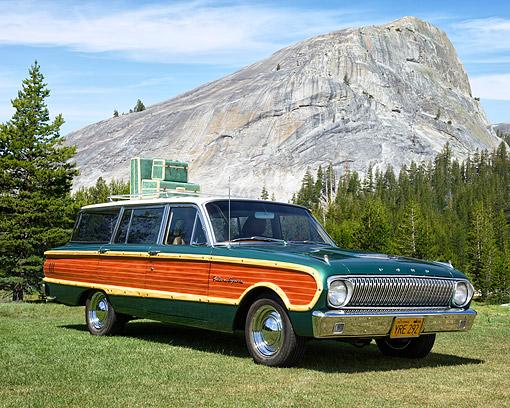 AUT 22 RK3805 01 © Kimball Stock 1962 Ford Falcon Squire Wagon Green With Wood Panels 3/4 Front View On Grass By Trees And Mountain