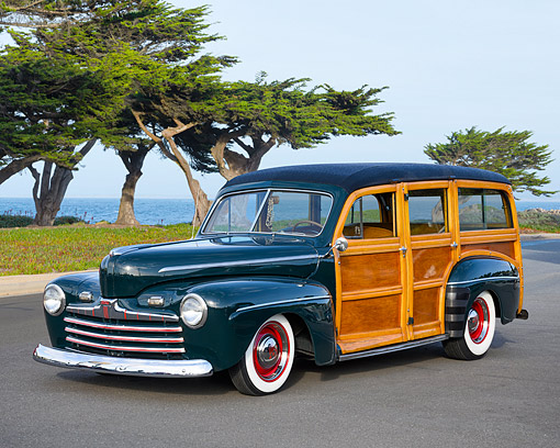 AUT 22 RK3815 01 © Kimball Stock 1945 Ford Woody Wagon Dark Green 3/4 Front View By Ocean
