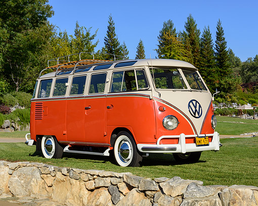 AUT 22 RK3830 01 © Kimball Stock 1961 Volkswagen 23-Window Deluxe Bus Red And White 3/4 Front View By Trees