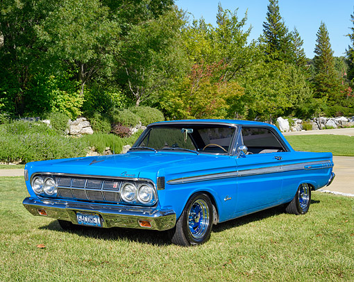 AUT 22 RK3855 01 © Kimball Stock 1964 Mercury Comet Caliente Blue 3/4 Front View On Grass By Trees