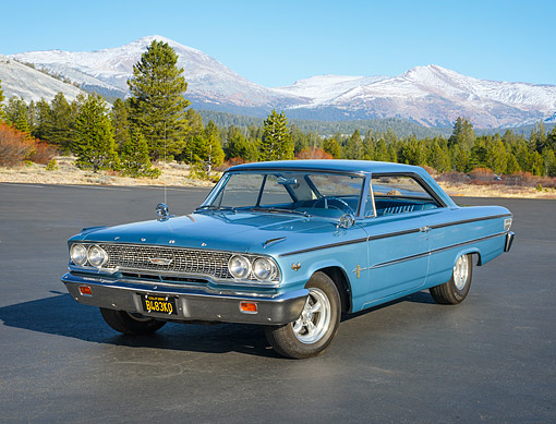 AUT 22 RK3882 01 © Kimball Stock 1963 1/2 Ford Galaxie 500 406 Fastback Blue 3/4 Front View On Pavement By Forest And Snowy Mountains