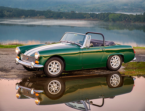 AUT 22 RK3902 01 © Kimball Stock 1969 Austin-Healey Mark IV Sprite Convertible Green 3/4 Front View By Water At Sunset