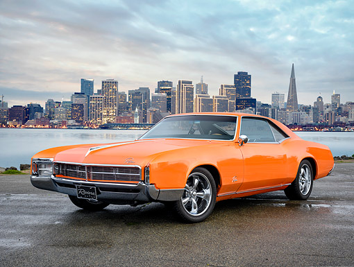 AUT 22 RK3917 01 © Kimball Stock 1967 Buick Riviera Orange 3/4 Front View On Pavement By City