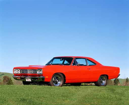AUT 22 RK0005 02 © Kimball Stock 1969 Plymouth Road Runner Red 3/4 Side View On Grass Blue Sky