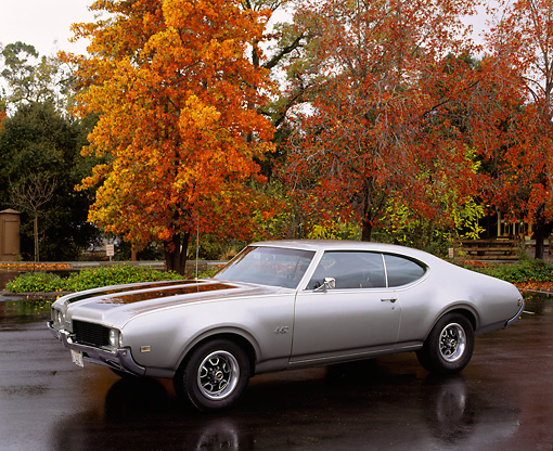 AUT 22 RK0140 05 © Kimball Stock 1969 Oldsmobile 442 Silver  3/4 Front View On Pavement By Fall Trees