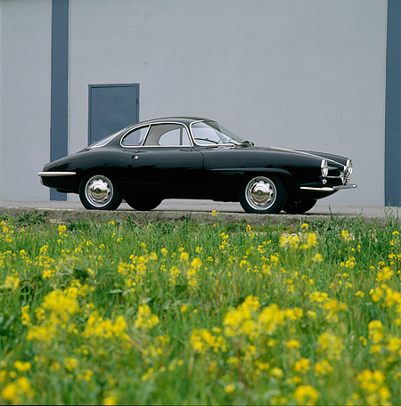AUT 22 RK0171 01 © Kimball Stock 1965 Alfa Romeo Giulietta SS Slight 3/4 Front View On Pavement By Yellow Flowers