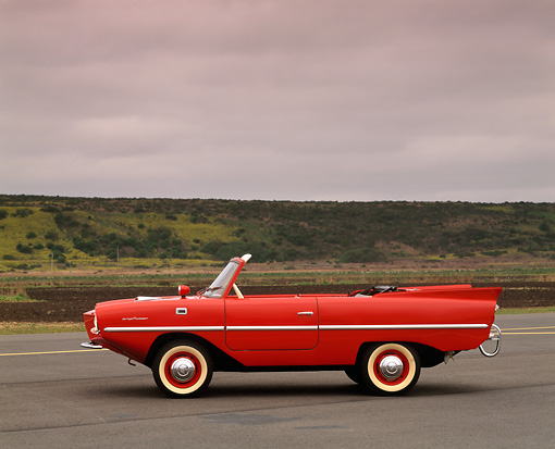 AUT 22 RK0184 02 © Kimball Stock 1964 Amphicar Convertible Red Profile View On Pavement Gray Clouds
