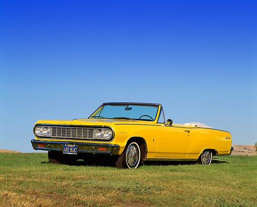 AUT 22 RK0233 01 © Kimball Stock 1964 Chevrolet Chevelle Malibu Convertible Yellow 3/4 Front View On Grass Hill