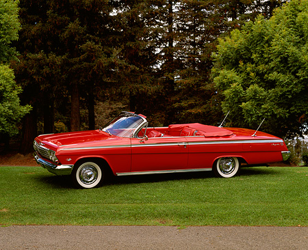 AUT 22 RK0239 02 © Kimball Stock 1962 Chevy Impala Super Sport Convertible Red 3/4 Side View On Grass Hill By Trees