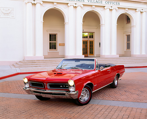 AUT 22 RK0459 02 © Kimball Stock 1965 Pontiac GTO Convertible Red 3/4 Front View On Pavement By Building Headlights On